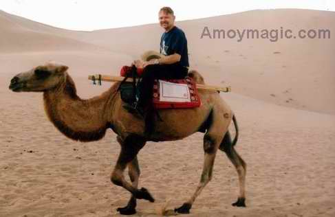 Bill rides a camel near Dunhuang in a West China desert