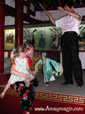 Quanzhou master puppeteer, Mr. Xia Rong Feng, entertains Ms. Jimmy Langley and her daughter Emma, at the Quanzhou Marionette Troupe museum and stage.
